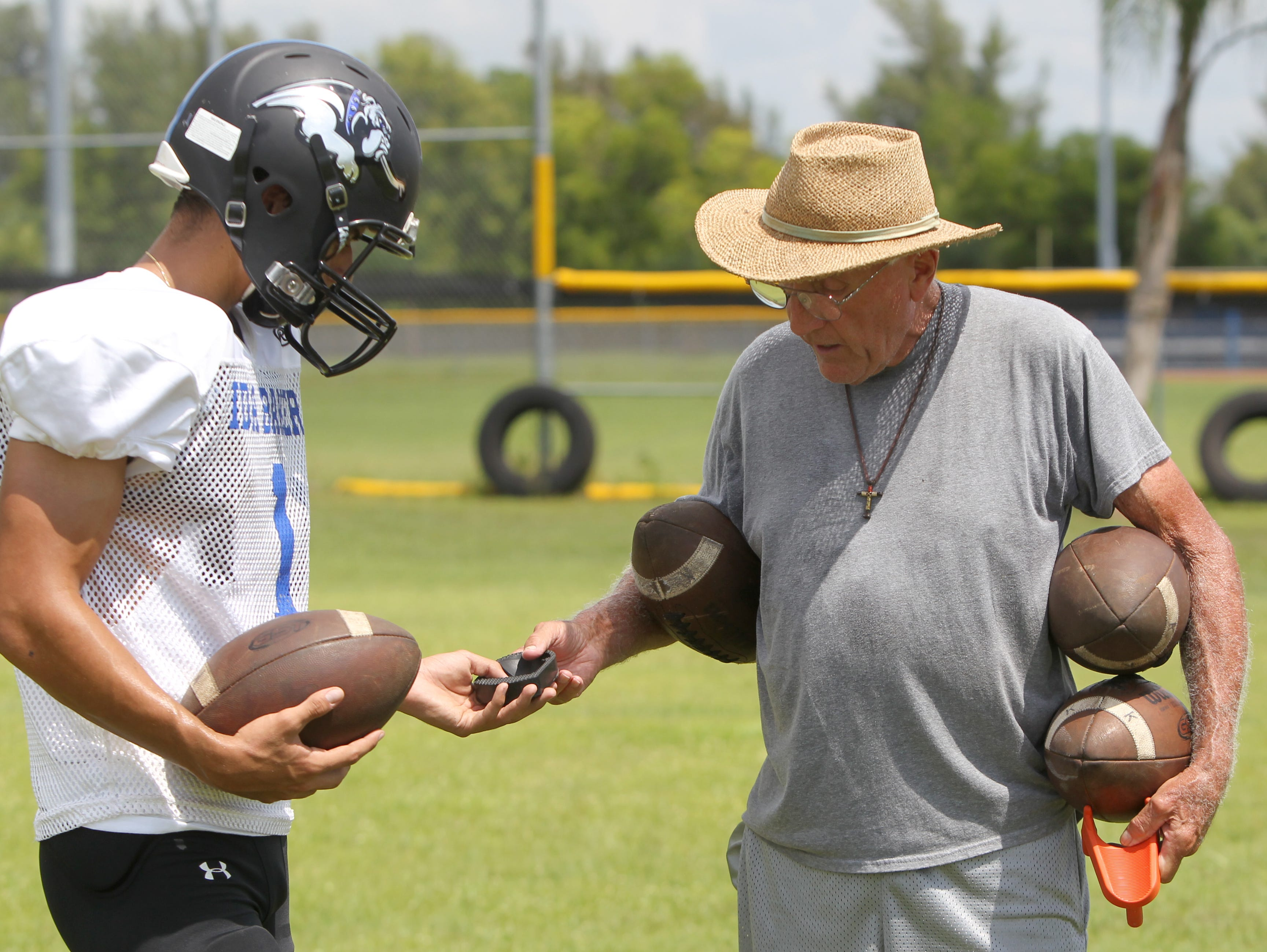 Dick O'Brien, right, helps kicker David Montoya with his form at Ida Baker practice Wednesday in Cape Coral.