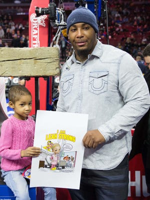 Bengals defensive tackle Devon Still and his daughter, Leah, courtside before ringing the ceremonial bell before a Sixers-Warriors game on Feb. 9.