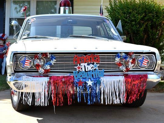 Classic cars, including this treasure entered by Julie Coley and her husband, were trimmed in patriotic fanfare for the annual Kell House Museum's Fourth of July parade.