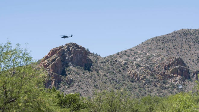 A helicopter hovers over the mountains along the U.S.-Mexico border near Sasabe in June 2017. A Border Patrol agent was assaulted in the area Nov. 17, 2017.