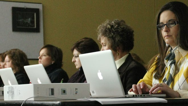 C. Todd Sherman Tupelo Public School teachers including Christy Bonds, right, try out their new laptop computers during a training workshop at the Hancock Leadership Center on Monday.