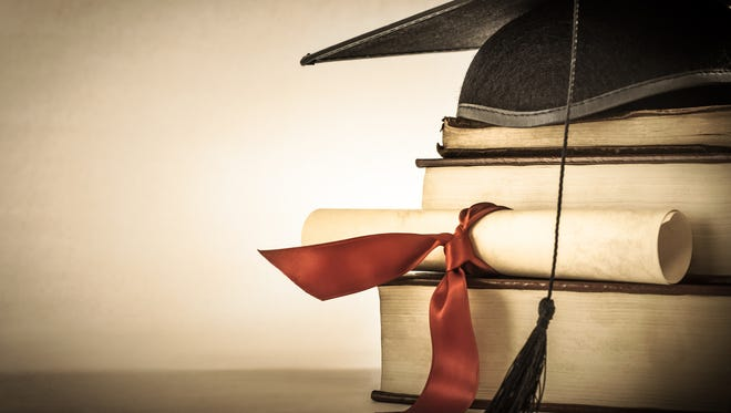 A mortarboard and graduation scroll, tied with red ribbon, on a stack of old battered book with empty space to the left.  Slightly undersaturated with vignette for vintage effect.