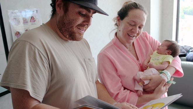 Joseph Roman and Pauline Cleary read a book to their newborn daughter, Juliette, who was born at Vassar Brothers Medical Center. The book is part of the AAUW Leading to Reading project, which provides a free book to all parents of newborns at the Poughkeepsie hospital. The program encourages parents to read to their children starting at infancy.