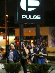 People gather outside of Pulse nightclub in Orlando on Monday, Dec. 12, 2012. Mourners were later allowed inside the fenced area at Pulse for a vigil to mark the 6-month anniversary of the shootings.   (Jacob Langston/Orlando Sentinel via AP)