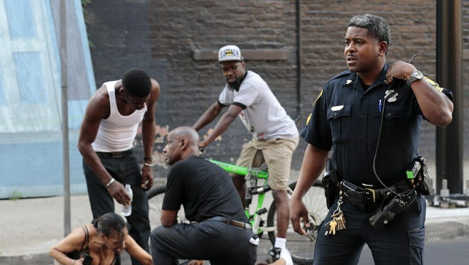 Police respond while State Senator Cecil Thomas, middle, and bystanders tend to a shooting victim while he lay near the intersection of Race and Elder Streets, across from Findlay Market, where has was shot during a three-person shootout about 7:00 p.m. in the Over-the-Rhine neighborhood of Cincinnati, Ohio, on Monday, June 22, 2015. The victim was transported to University of Cincinnati Medical Center where he died. Thomas was in the neighborhood taking part in a peace march through the streets just moments before the gunfire.
