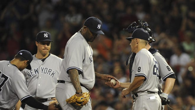 Yankees starter CC Sabathia hands the ball to manager Joe Girardi after being relieved during the sixth inning against the Red Sox on Sunday.