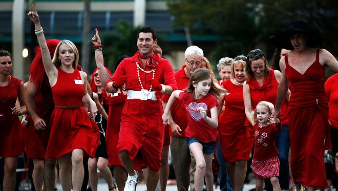 A crowd of people run down Park Street at 5th Ave South during the third annual American Heart Association's Go Red For Women Red Dress Dash event on National Wear Red Day on Friday, Feb. 7, 2014 in Naples, Fla. The event celebrates American Heart Month, and brings attention to heart disease as the number one cause of death for women.