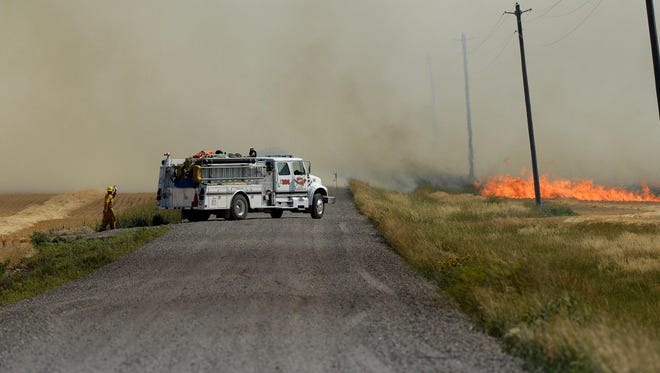 An engine from the Black Eagle Fire Department prepares to fight a fire threatening to jump Vineyard Road on Tuesday afternoon.