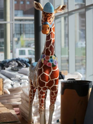 One of the characters of Carol Ann's Carousel, a giraffe, was unveiled as installation began in Smale Riverfront Park on Tuesday, April 21.