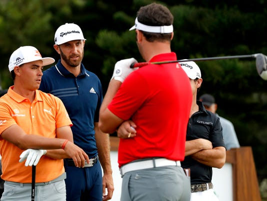 Rickie Fowler, left, Dustin Johnson, center, and Jon Rahm, with club, talk on the 18th tee box during the final round of the Tournament of Champions golf event, Sunday, Jan. 7, 2018, at Kapalua Plantation Course in Kapalua, Hawaii. (AP Photo/Matt York)