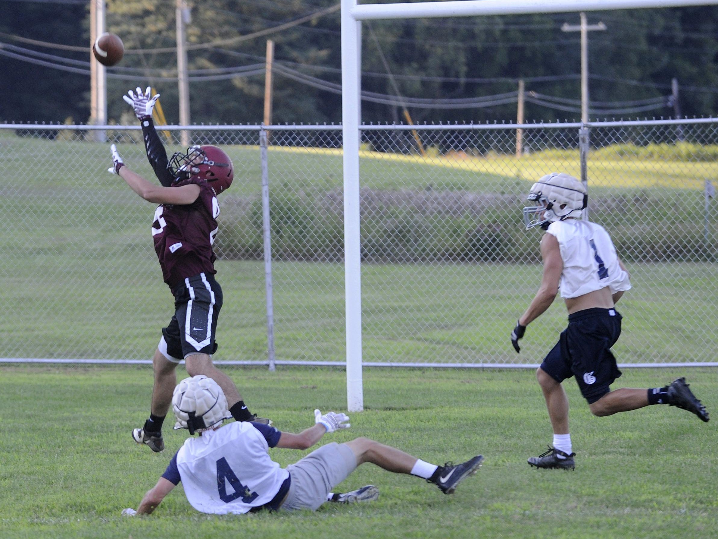 Newark's Iziah Culver stretches for a long pass against defense from Granville's Jake Peterson and Thaddeus Winston during a 7-on-7 passing scrimmage Thursday at Evans Athletic Complex.