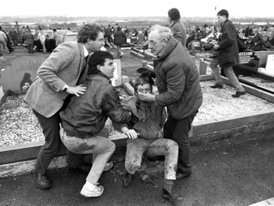 FILE - In this March 16, 1988 file photo an injured man is aided by mourners, including Sinn Fein vice president Martin McGuinness, left, at Milltown Cemetary, Belfast, after a gun and bomb attack killed three and left four seriously injured, at the funerals of three IRA members killed in Gibraltar. McGuinness, the Irish Republican Army commander who led his underground, paramilitary movement toward reconciliation with Britain, and was Northern Ireland's deputy first minister for a decade in a power-sharing government, has died, his Sinn Fein party announced Tuesday, March 21, 2017,  on Twitter. He was 66.