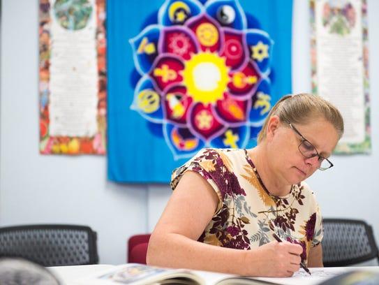 Kelley Croisdale colors her mandala during a course