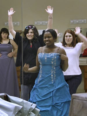 Anna Reilly, second from left, and Katie Buteau, right, celebrate as Jaraycia Bell, 18, from Emmerich Manual High School finds her dress, at the Prom Dress Giveaway held at the Brookville Road Community Church in New Palestine, Saturday, March 2, 2013.  The fifth annual event is hosted by Studio 52 Salon in New Palestine. Girls were allowed to try on donated prom dresses and to take one to wear for their prom this year.   Buteau, a math teacher at Manual got about ten students to come to the event.