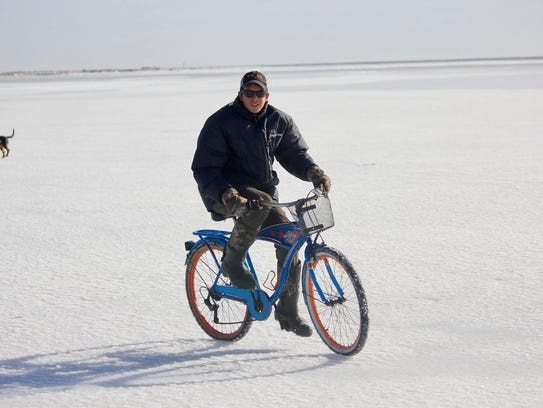 Trent Pruitt rides a bicycle on the ice near Tangier,