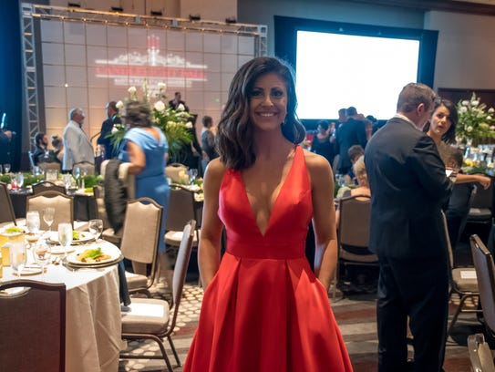 Nicole Rye wore a red ballgown with full skirt and