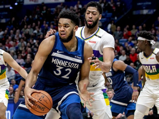 Minnesota Timberwolves center Karl-Anthony Towns (32) works against New Orleans Pelicans forward Anthony Davis during the first half of an NBA basketball game in New Orleans, Friday, Feb. 8, 2019. (AP Photo/Scott Threlkeld)