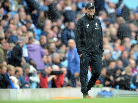 Liverpool's coach Juergen Klopp walks on the pitch during heavy rainfall after the English Premier League soccer match between Manchester City and Liverpool at the Etihad Stadium in Manchester, England, Saturday, Sept. 9, 2017. Manchester defeated Liverpool by 5-0. (AP Photo/Rui Vieira)