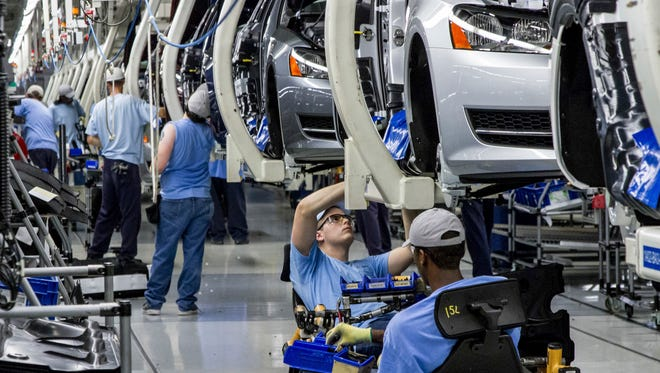 In this 2013 file photo, workers assemble Volkswagen Passat sedans at the German automaker's plant in Chattanooga, Tenn. Volkswagen will announce its future strategy which might include job cuts in a press conference on Friday, Nov. 18, 2016. (AP Photo/Erik Schelzig, file)
