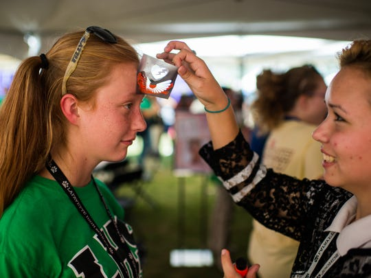 Kaitlyn Thompson, 16, watches as Shelby Vincent, 17, stencils a design onto her forehead during the High School Nation tour stop at Lafayette High School in Lafayette, La., Friday, Sept. 25, 2015. LHS is one of 50 schools in the country to be chosen for the High School Nation tour which brings musicians and interactive exhibits to school campuses.