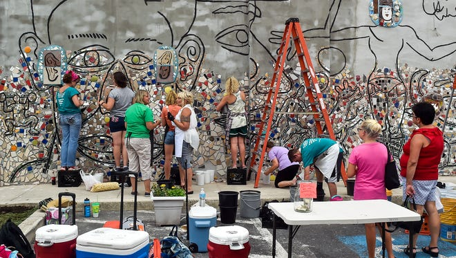 Members of the community work together to complete  a mosaic with the help of Isaiah Zagar on Staurday, July 16, 2016 outside of Main Street Deli in downtown Chambersburg.