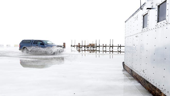A pick-up truck kicks up water coming off Lake Winnebago Tuesday near Wendt's on the Lake. Warm temperatures and rain on Tuesday caused a layer of standing water on the ice, and ice shanties were put up on blocks to avoid getting frozen into the lake. Lower temperatures are expected on Wednesday and Thursday in advance of the season, which opens on Saturday morning.
