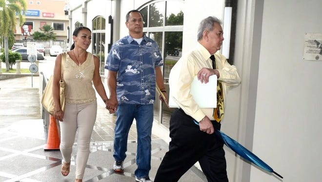 In this March 29, 2017, file photo, Mark Smith, center, walks hand-in-hand with Clare Calvo, his ex-wife, as they are led into the District Court of Guam building by David Lujan.