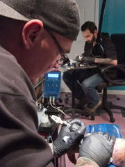 Tattooist Britt Stockley inks a dragon design on the left forearm of customer Jason Ray at the recently opened Metro Studios in downtown Howell. In the background is co-owner Igor Kocherga.