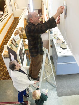 Hamburg Township Historical Museum President Wayne Burkhardt smooths out mudding on repaired drywall damaged from a leaky roof at the Hamburg Historical Museum in 2015 before major renovations and repairs were done. Holding the ladder are his late wife Nora Lee Burkhardt, and their 3-year-old great-grandson, Winston Nausieda.