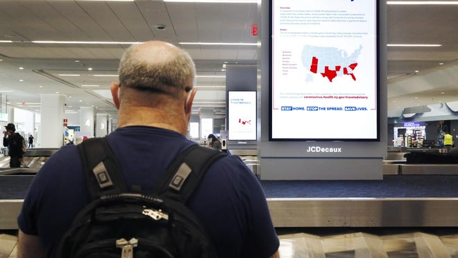 A man awaits his luggage in the baggage claim area of Terminal B at LaGuardia Airport, Thursday, June 25, 2020, in New York. New York, Connecticut and New Jersey are asking visitors from states with high coronavirus infection rates to quarantine for 14 days.