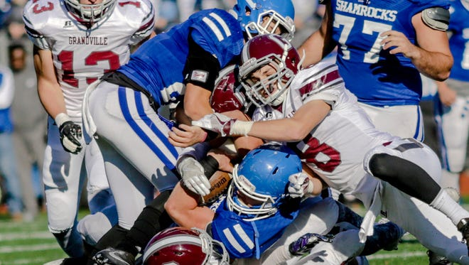 Novi Detroit Catholic Central's Nick Jenkins tangle with Grandville's Aaron Brokaw, Jalen Raniga, Connor Gifford, and Jake Tipton during CC's 28-14 win in the Division 1 regional final at Catholic Central Saturday.