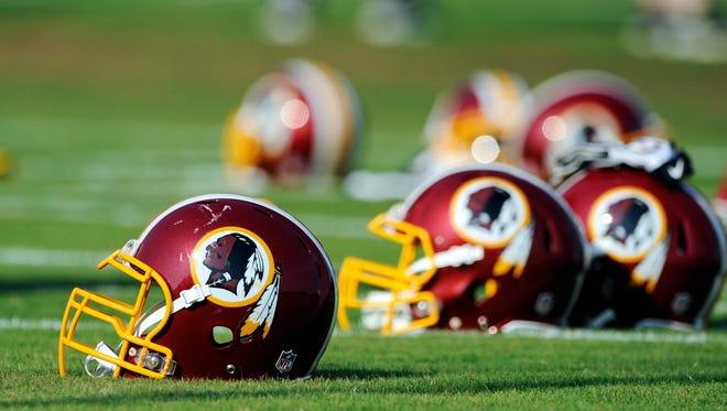 Washington Redskins helmets sit on the field during an NFL football minicamp in Ashburn, Va.