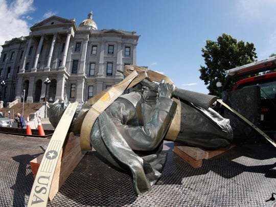 The Civil War Monument statue is strapped on the back of a flatbed tow truck after it was toppled from its pedestal in front of the State Capitol Thursday, June 25, 2020, in Denver. The monument, which portrays a Union Army soldier and was erected in 1909, was targeted during demonstrations over the death of George Floyd before the statue was pulled down overnight by four individuals. (AP Photo/David Zalubowski)