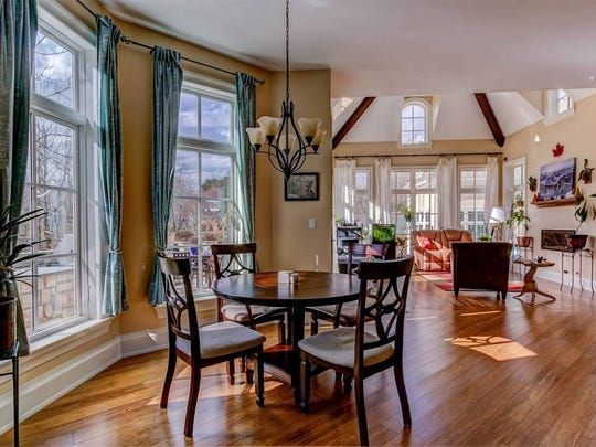 The home's cathedral ceilings and abundant windows invite sunlight to bathe the open floor plan and hardwood floors.