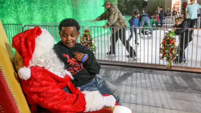 Deshun Latimer, right, of Anderson, tells Santa Claus on Thursday what toys he would like for Christmas at the Ice-skating rink at Carolina Wren Park in Anderson.