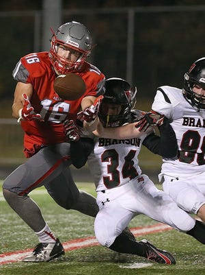 Chase Allen makes a catch for a first down against Kyle Hunn (34) and Nathan Piche (98) of visiting Branson on Friday.