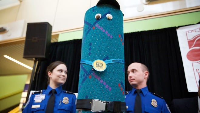 TSA officers Andrea Green, left,  and Edmund Gray stand beside a piece of dressed up old carpet from the terminal at Portland International Airport during a press conference in Portland Ore., March 20, 2015.