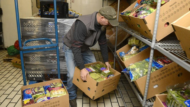 Mike Goulet stocks a shipment of produce in a cooler at the Great Falls Food Bank.