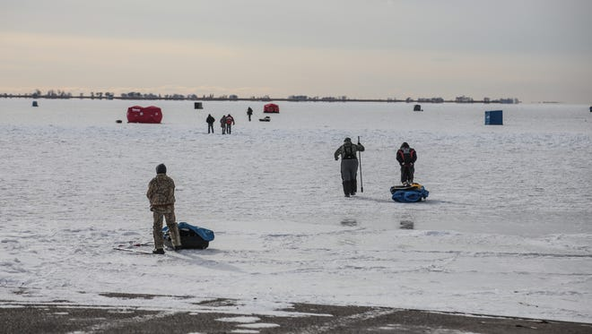 People make their way out onto the ice to fish on the frozen Lake St. Clair in Ira Township on December 28, 2017.