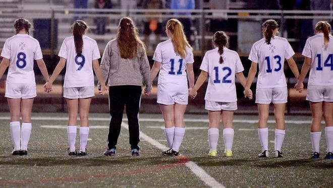 Loyola players join hands in prayer before their game against Teurlings Catholic on Friday. In  the center is Ally Peters  who was unable to play in the game due to an illness.
