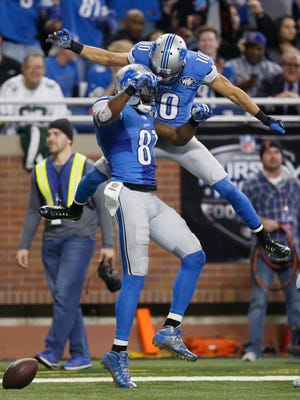 Calvin Johnson, left, and Corey Fuller celebrate in the end zone after a touchdown last season.
