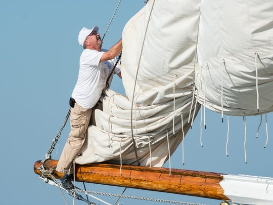 A crew member of the Rebecca T. Ruark fixes a sail during the Deal Island Skipjack Races on Monday, Sept. 4, 2017.