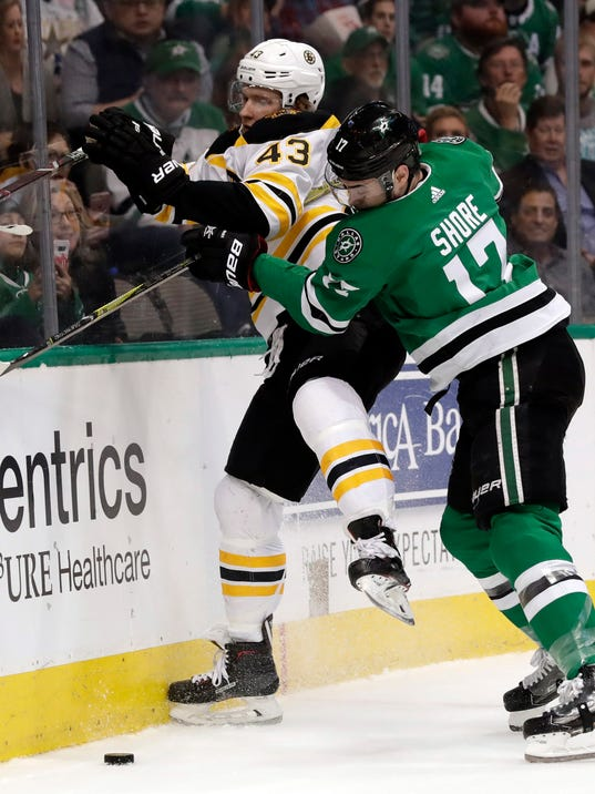 Boston Bruins left wing Danton Heinen (43) and Dallas Stars center Devin Shore (17) compete for control ofthe puck in the first period of an NHL hockey game in Dallas, Friday March 23, 2018. (AP Photo/Tony Gutierrez)