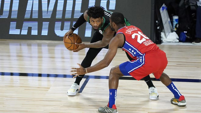Celtics guard Marcus Smart keeps the ball from the Philadelphia 76ers' Alec Burks during the first half of their first-round playoff game Monday in Lake Buena Vista, Fla.