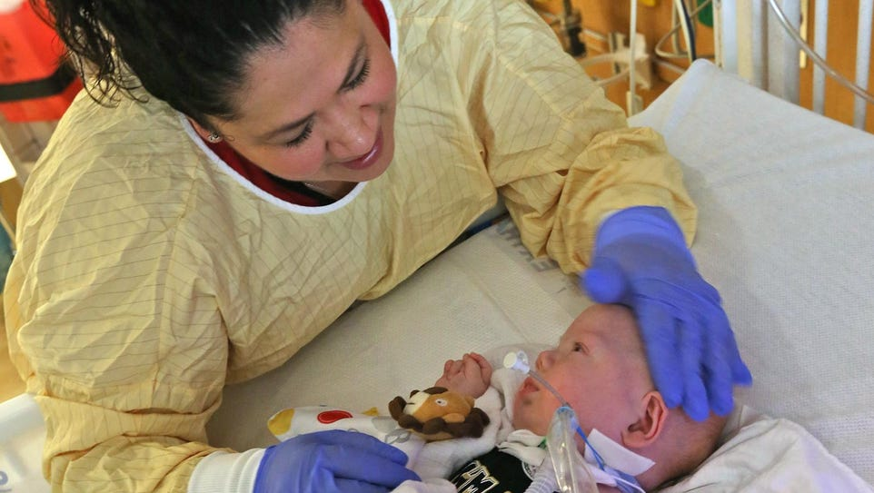 Charmaine Mercado, RN, comforts 5-month-old Caleb Fussner