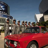 Models pose with a classic Alfa Romeo on the opening day of the Los Angeles Auto Show.