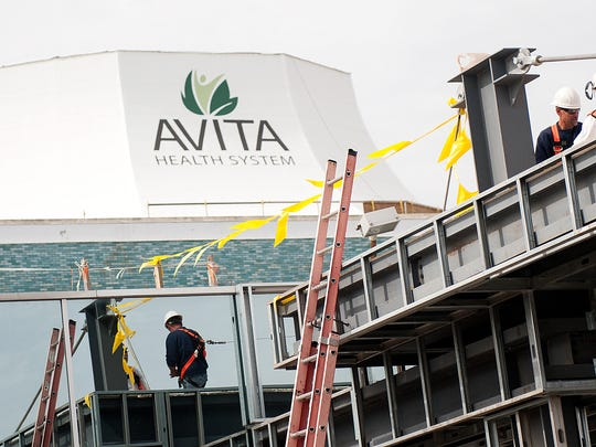 Construction workers build on top of the awning that stretches out of the Foster entrance of the new Avita Health System building at the Richland Mall.