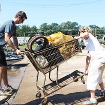 Bryce Hoggatt and Elizabeth Allstaedt lift a grocery cart filled with garbage they fished out of the Ouachita River out of a boat at the Forsythe Boat Launch during the Ouachita River Water Sweep on Sept. 10.