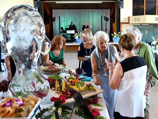 Maija Gadient talks to attendees of Friday's fundraising gala next to a manatee-shaped ice sculpture.