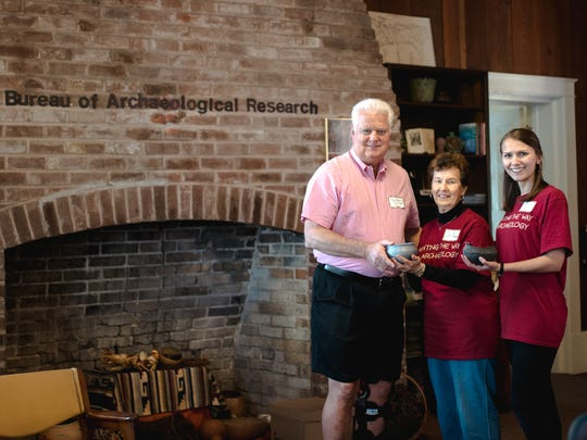 Dr. de Grummond and Jessica Rassau pose with Secretary of State Ken Detzner after discussing two ancient pottery artifacts.